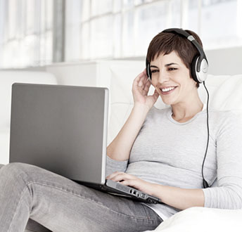 Young Woman Sitting on Chair Smiling Wearing Headphones